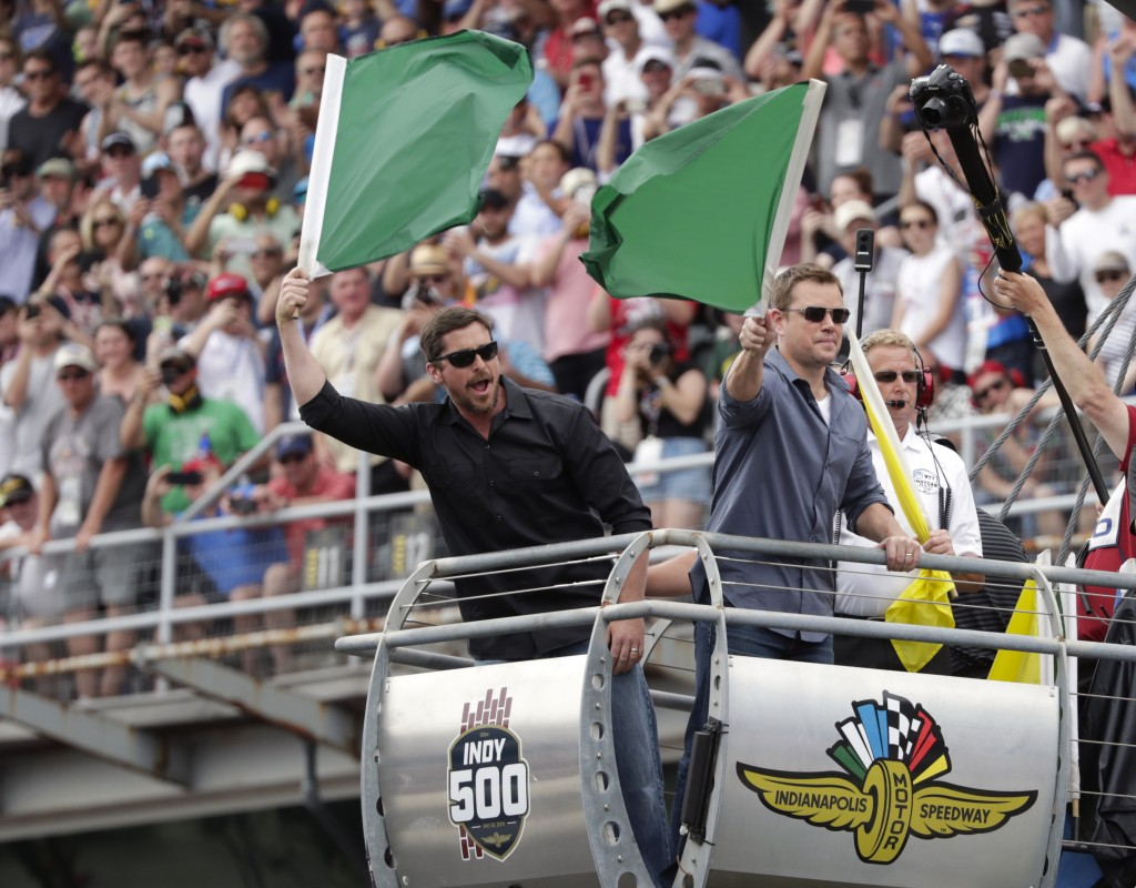 FILE - In this May 26, 2019, file photo, actors Christian Bale, left, and Matt Damon wave green flags to start Indianapolis 500 IndyCar auto race at I...