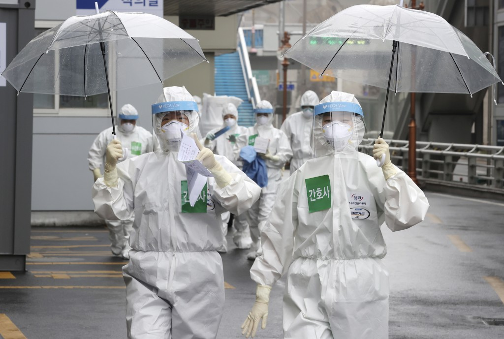 Medical staff members arrive for a duty shift at Dongsan Hospital in Daegu, South Korea, Friday, March 27, 2020. The new coronavirus causes mild or mo...