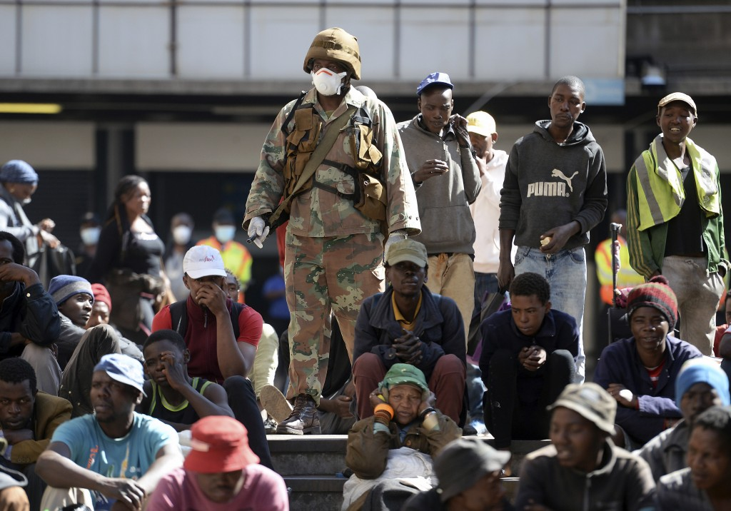A soldier watches homeless people who were rounded up in downtown Johannesburg Friday, March 27, 2020, after South Africa went into a nationwide lockd...