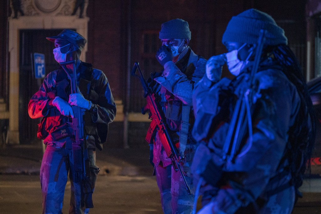Lit by police lights, South African Defense Forces patrol downtown Johannesburg, South Africa, Friday, March 27, 2020. Police and army started patroll...