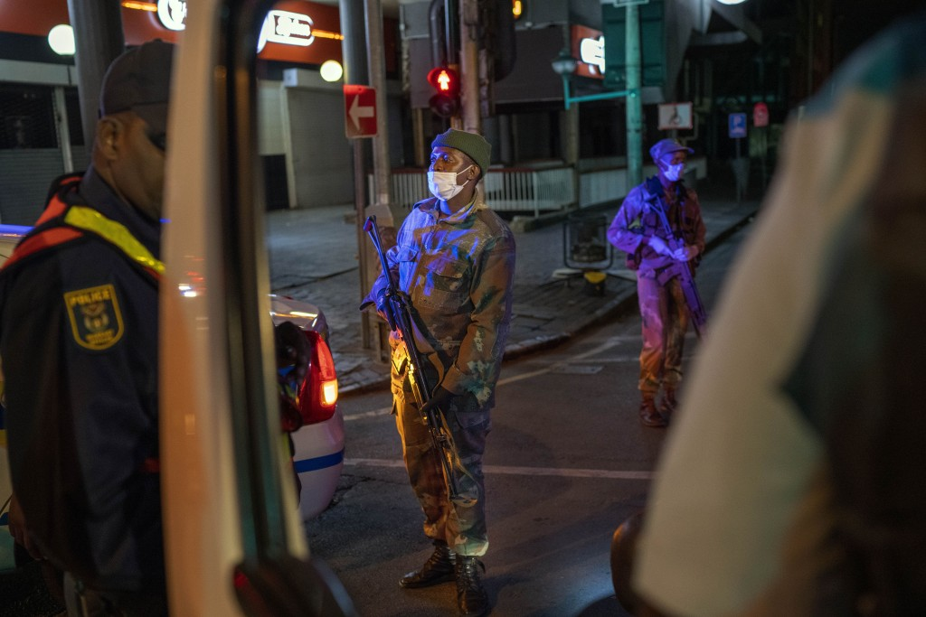 South African Defense Forces and police check a minibus driver who violated the lockdown downtown Johannesburg, South Africa, Friday, March 27, 2020. ...