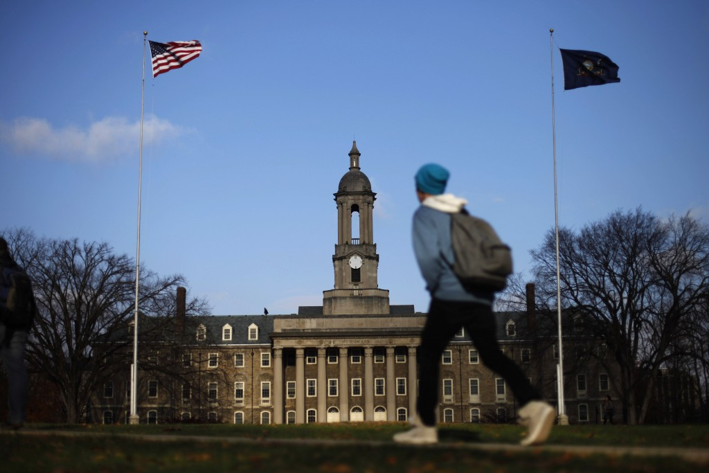 FILE – In this Friday, Nov. 11, 2011, file photo, a student walks in front of the Old Main building on the Penn State campus in State College, Pa. U.S...