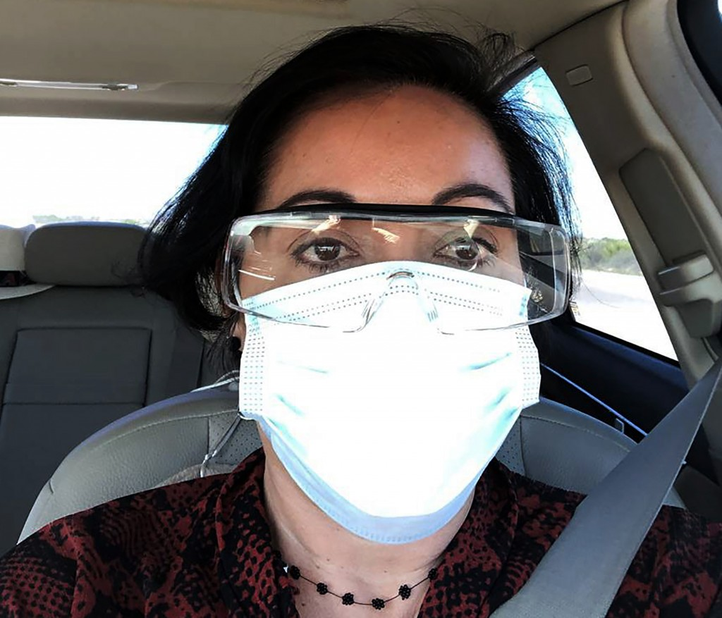 This March 23, 2020 photo provided by Margarita Silva shows her outside the La Palma Detention Center in Eloy, Ariz., wearing her husband's land surve...