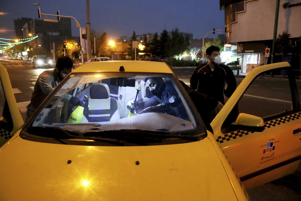 FILE — In this Wednesday, March 25, 2020 file photo, a member of the Iranian Revolutionary Guard disinfects a taxi to help prevent the spread of the n...