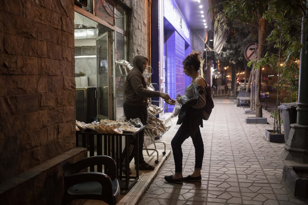 """In this Feb. 20, 2020 photo, transgender woman and activist Malak el-Kashif buys bread from a vendor on a street in Cairo, Egypt. """"If I wanted to hide..."""