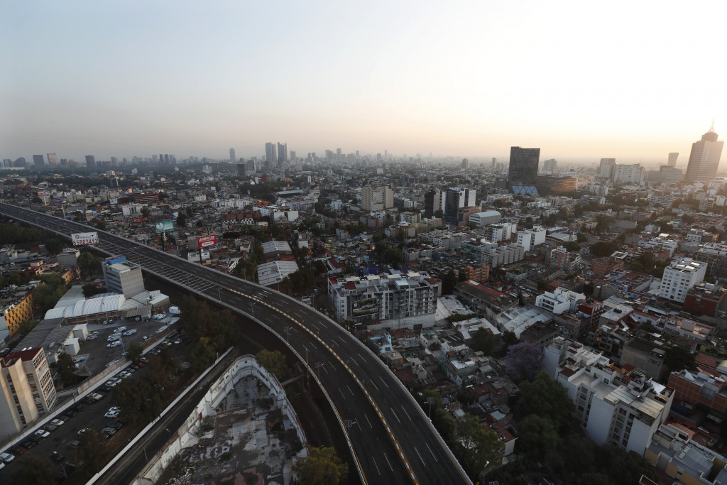 An elevated highway nearly devoid of traffic cuts into Mexico City, Sunday, March 22, 2020. Many countries in Latin America have taken aggressive meas...