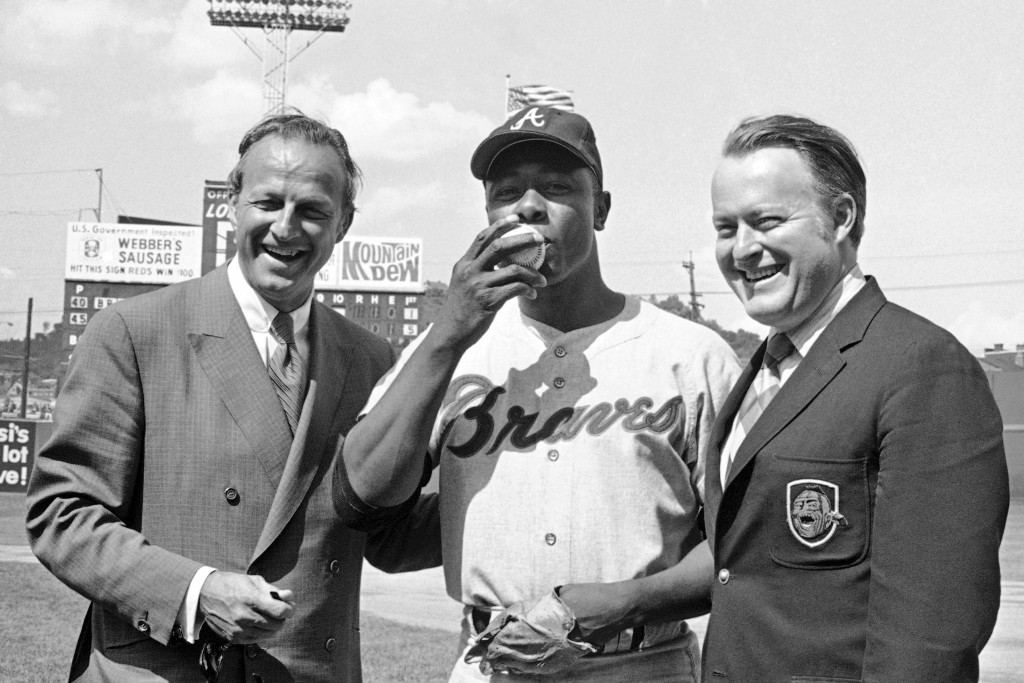 FILE - In this May 17, 1970, file photo, Atlanta Braves' Hank Aaron, center, who became the ninth player in Major League history to get 3,000 hits, ki...