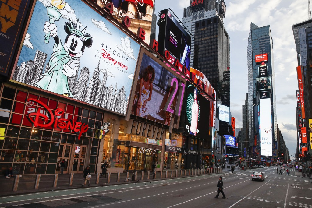 FILE - In this March 20, 2020, file photo, a police officer walks across an empty Seventh Avenue in a sparsely populated Times Square due to COVID-19 ...