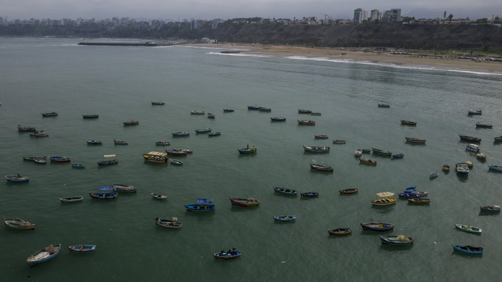 Small fishing boats are anchored near the Chorrillos dock in Lima, Peru, Thursday, March 26, 2020, on the second week of a government decreed state of...