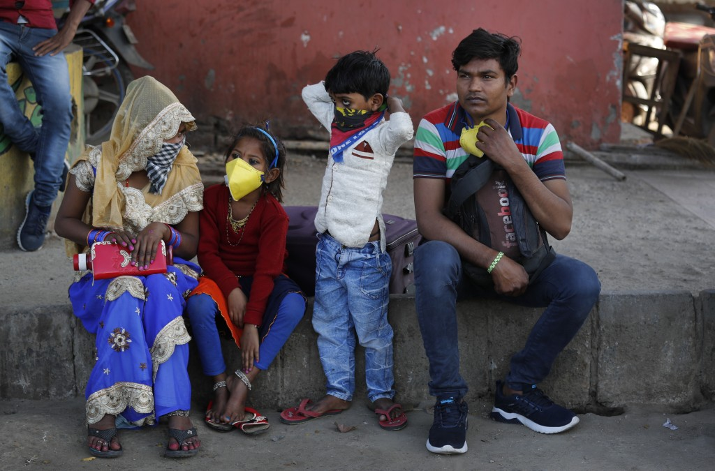 Migrant daily wage laborer Ram Bhajan Nisar and his family wait for transportation to travel to their hometown following a lockdown amid concern over ...