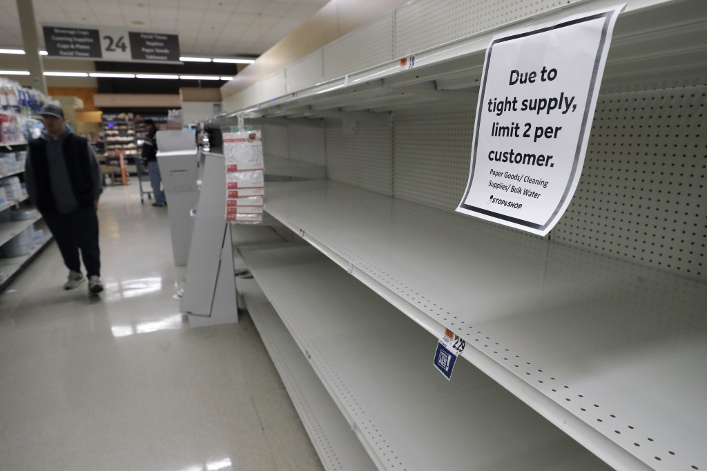 FILE - In this March 26, 2020, file photo, a passerby walks down an aisle with empty shelves where paper towels are normally on display at a grocery s...
