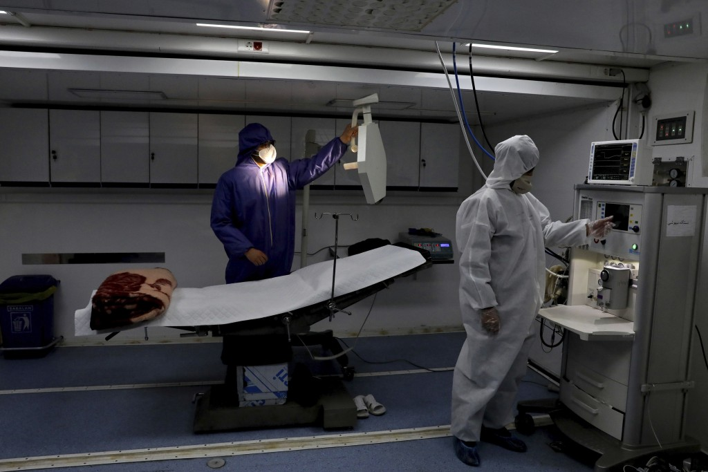 People in protective clothing work in a temporary 2,000-bed hospital for COVID-19 coronavirus patients set up by the Iranian army at the international...