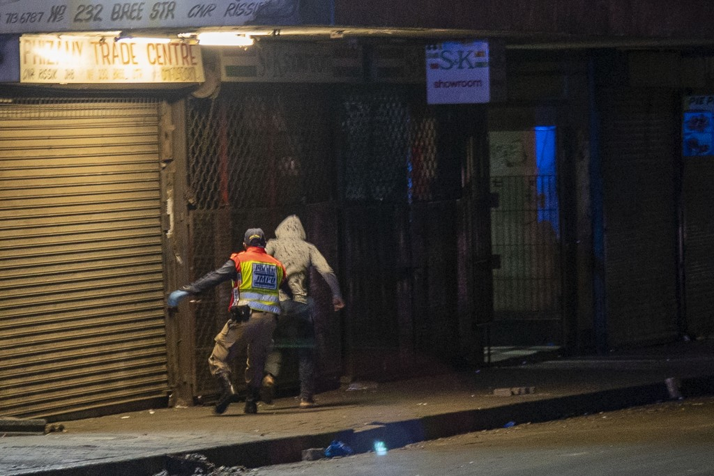 A police officer chases a man who violated the lockdown downtown Johannesburg, South Africa, Friday, March 27, 2020. Police and army started patrollin...
