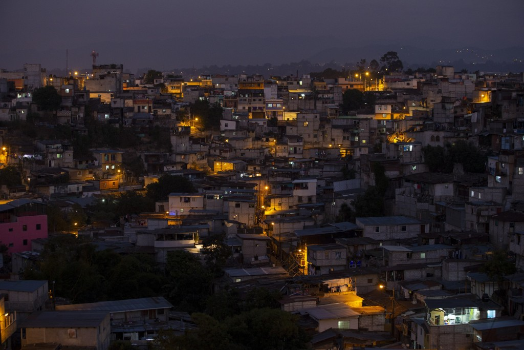 La Limonada neighborhood is illuminated by street lights during a curfew to help prevent the spread of the new coronavirus, in Guatemala City, Tuesday...