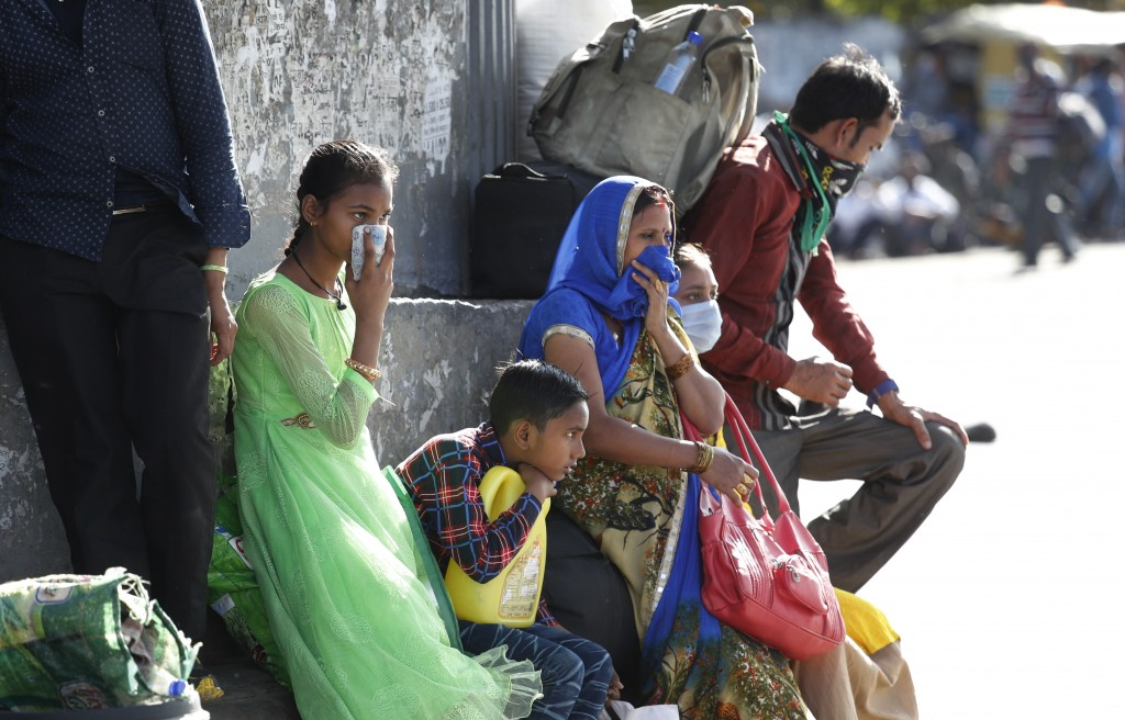A migrant family wait for transportation to travel to their respective villages following a lockdown amid concern over spread of coronavirus in New De...