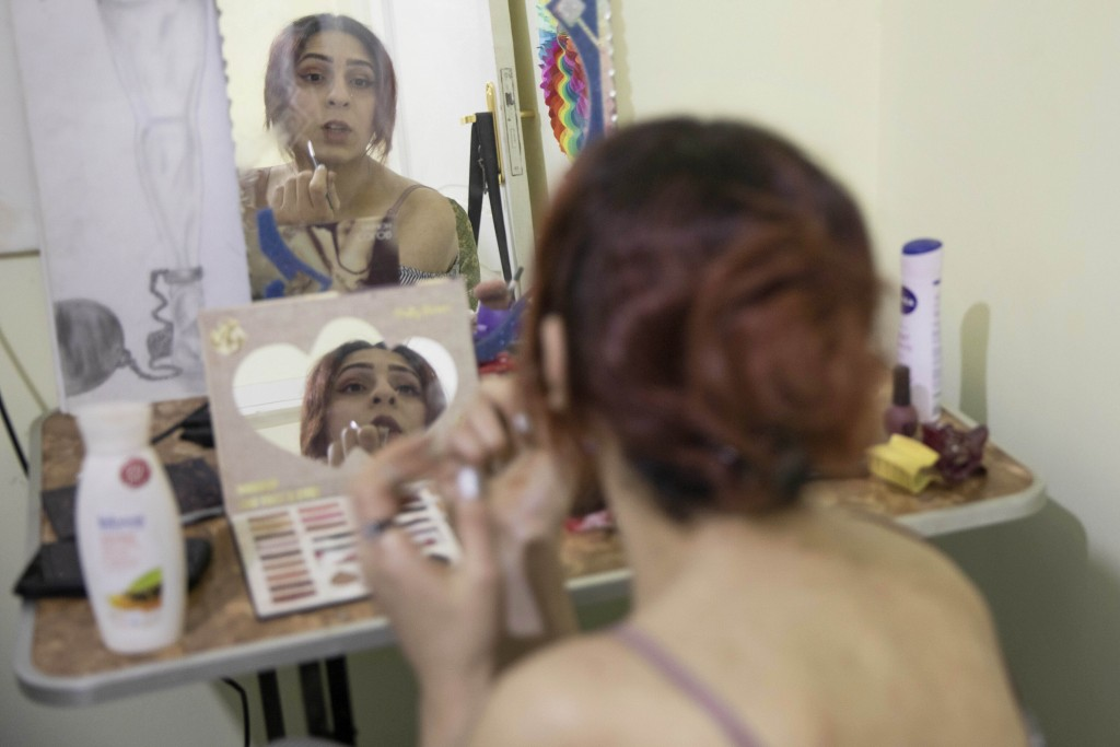 In this Feb. 18, 2020 photo, Egyptian transgender woman and activist Malak el-Kashif puts on makeup in her bedroom, in Cairo, Egypt. El-Kashif punctua...