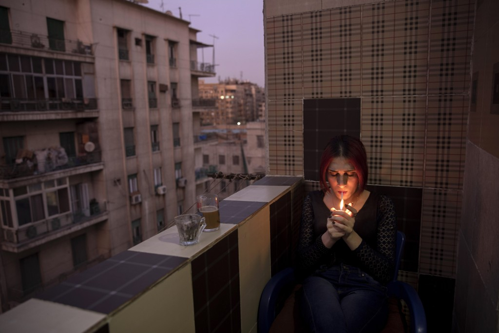 In this Oct. 28, 2019 photo, Egyptian transgender woman and activist Malak el-Kashif smokes a cigarette in the balcony of her apartment in Cairo, Egyp...