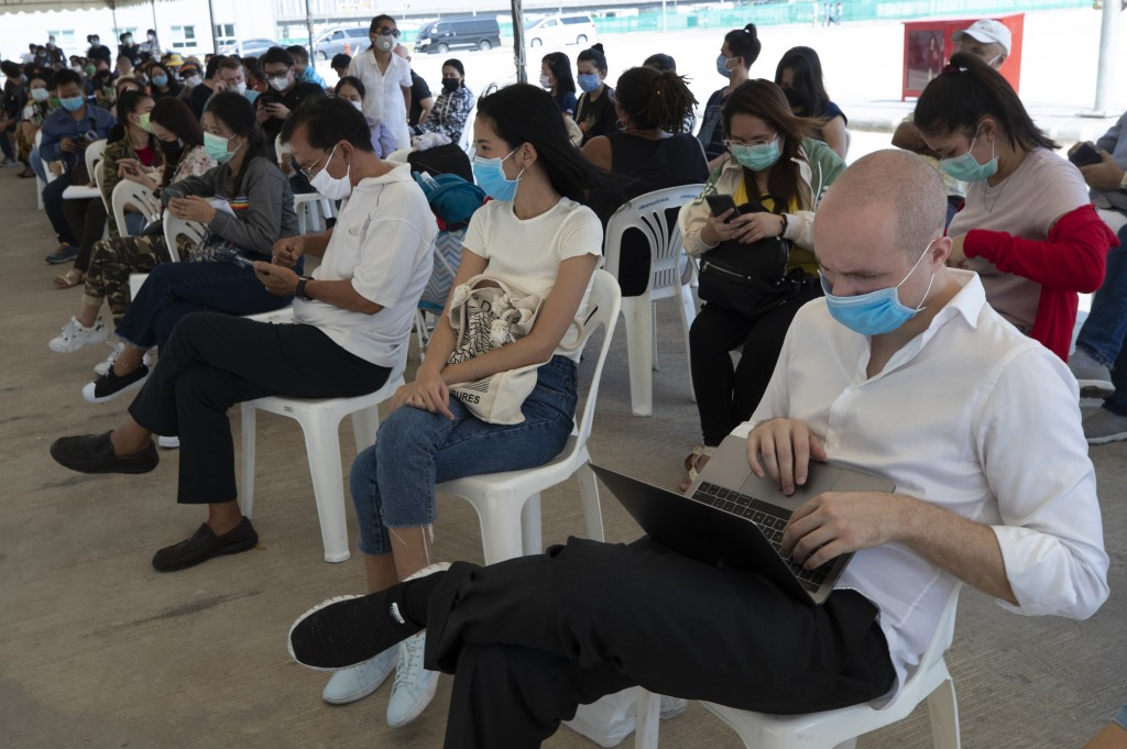 Tourists practice social distancing as they wait to extend their visa at Immigration Bureau in Bangkok, Thailand, Friday, March 27, 2020. Tourists acr...