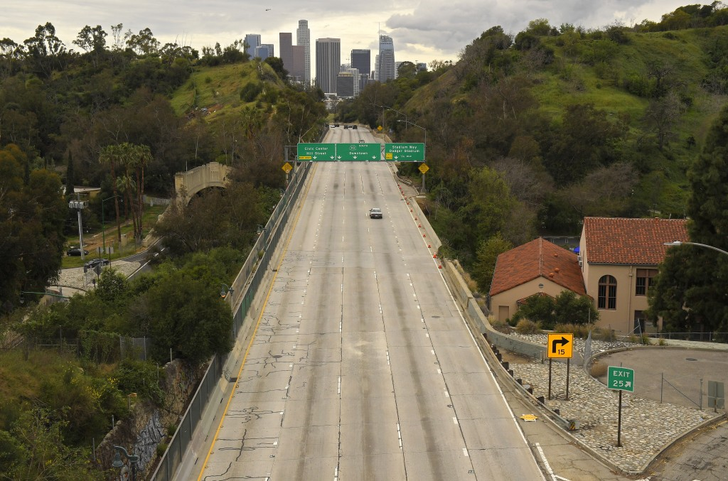 FILE - In this March 20, 2020, file photo, extremely light traffic moves along the 110 Harbor Freeway toward downtown during mid-afternoon in Los Ange...