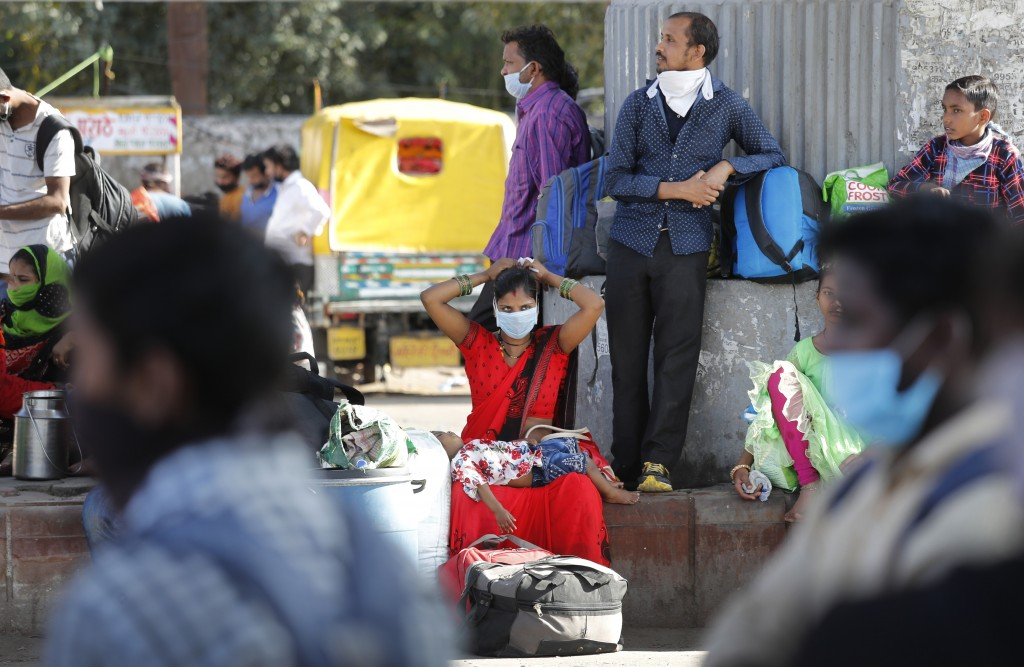 A migrant daily-wage laborer family wait for transportation to travel to their respective villages following a lockdown amid concern over spread of co...