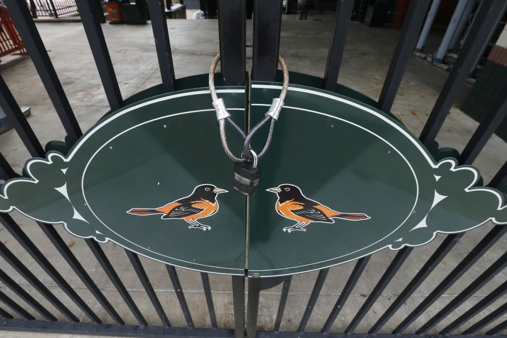 Locked gates and empty walkways are shown at Oriole Park at Camden Yards, home of the Baltimore Orioles baseball team, on what was to be opening day M...