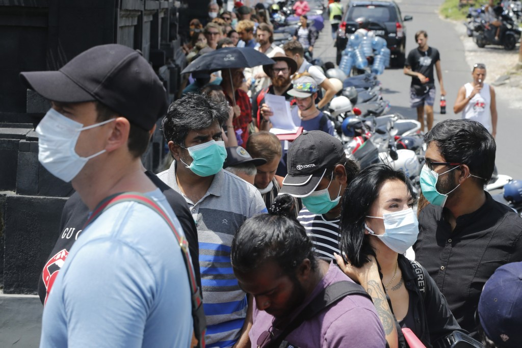 In this March 23, 2020 photo, foreign tourists who are unable to fly home due to the new coronavirus outbreak, queue up outside an immigration office ...