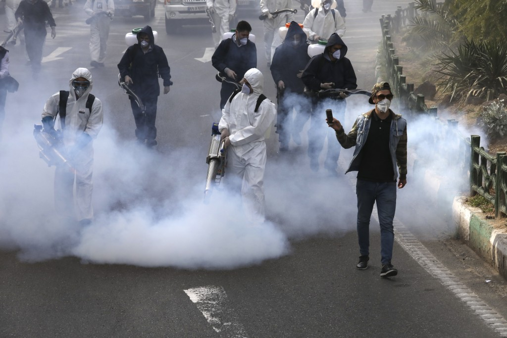 In this Friday, March 13, 2020 photo, firefighters disinfect a square against the new coronavirus as a man takes film, in western Tehran, Iran. Local ...