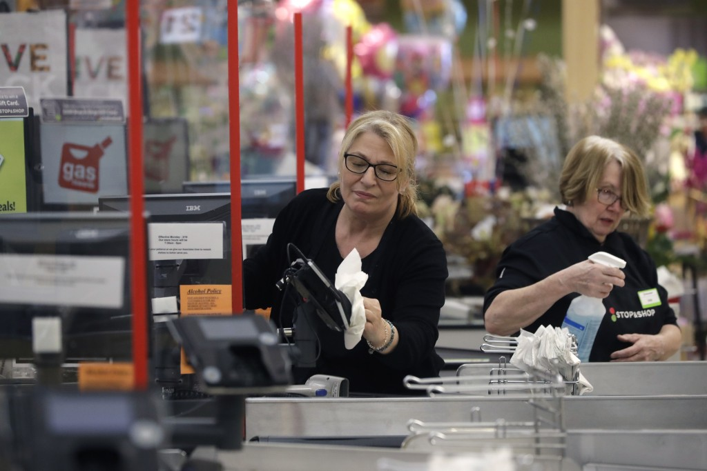 Cashiers at a grocery store sanitize a card reader and the checkout area, Thursday, March 26, 2020, in Quincy, Mass., as an extra precaution out of co...