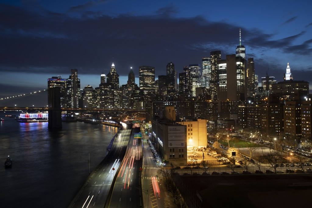 Cars head along FDR Drive next to the Manhattan skyline, Thursday, March 26, 2020, during the coronavirus outbreak in New York. Because of Gov. Andrew...