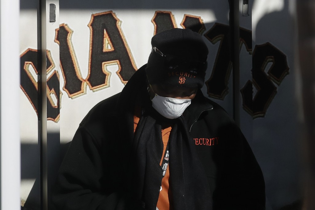 Security guard LeJuana Evans wears a mask while working a gate at Oracle Park, the San Francisco Giants' baseball ballpark, in San Francisco, March 26...