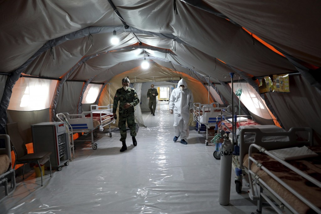 Iranian army soldiers work in a temporary 2,000-bed hospital for COVID-19 coronavirus patients set up by the army at the international exhibition cent...