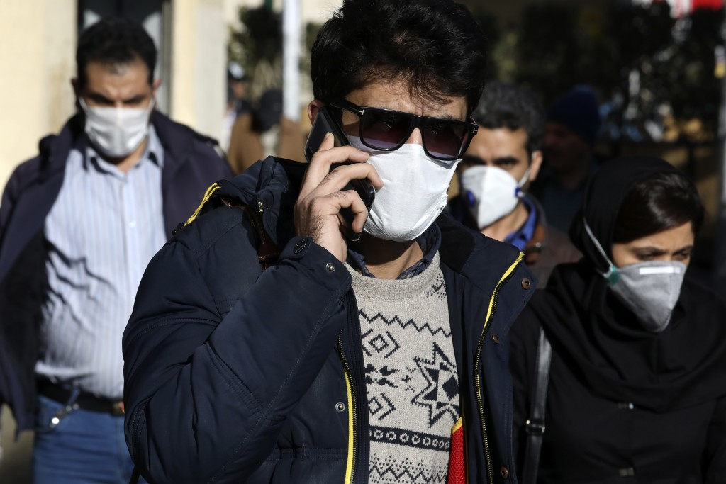 FILE — In this Monday, March 2, 2020 file photo, a man wearing a face mask, to help protect against the new coronavirus, speaks on his cellphone in do...
