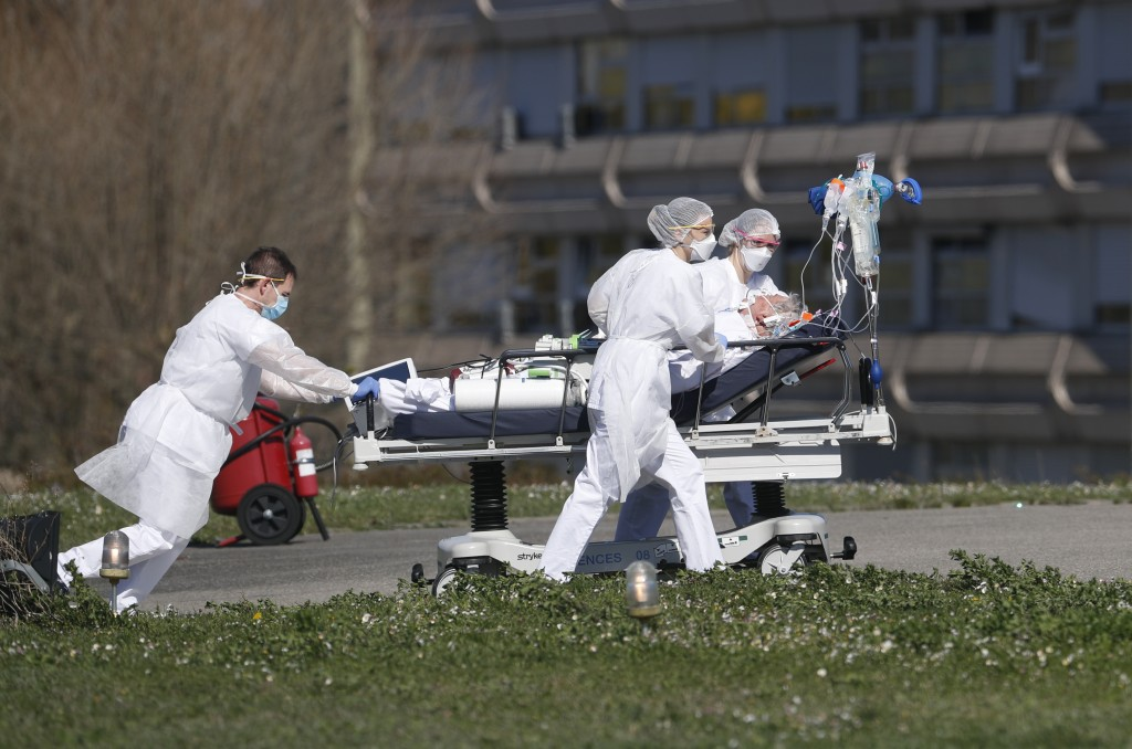 A victim of the COVID-19 coronavirus is evacuated by stretcher from the Mulhouse civil hospital in eastern France, Monday March 23, 2020. The Grand Es...