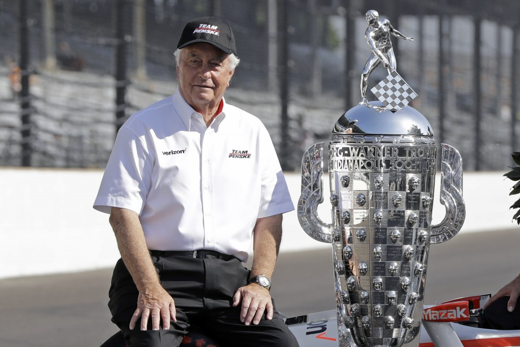 FILE - In this May 28, 2018, file photo, team owner Roger Penske poses beside the Borg-Warner Trophy after Penske driver Will Power won the Indianapol...