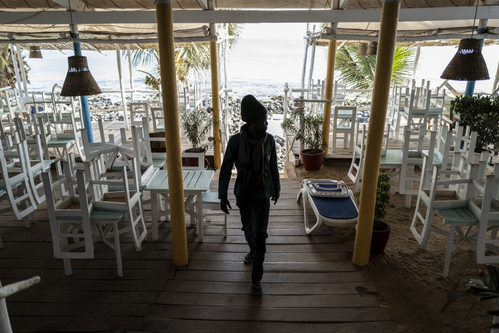 In this Thursday, March 26, 2020, photo, a security guard walks in a normally busy but now closed restaurant on a beach in Dakar, Senegal. As African ...