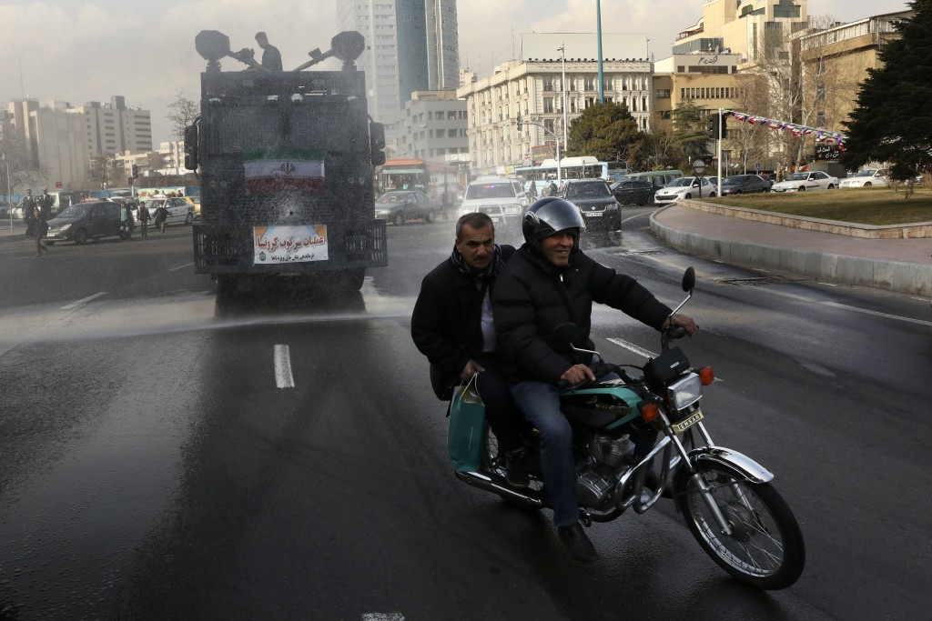 In this Sunday, March 1, 2020 photo, a police vehicle disinfects streets against the coronavirus, in Tehran, Iran. Local media reported Thursday, Marc...