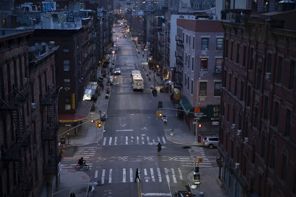 Bicyclists and a pedestrian pass through a quiet Manhattan street, Thursday, March 26, 2020, during the coronavirus pandemic in New York. Because of G...