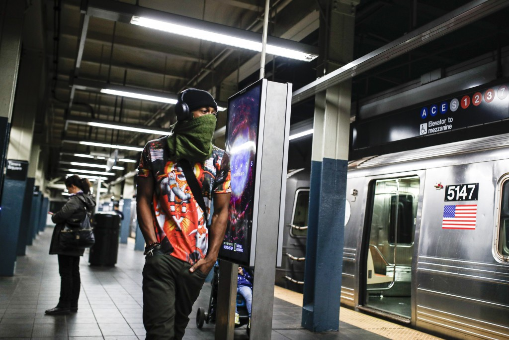 FILE - In this March 20, 2020, file photo, a subway customer walks a sparsely populated 42nd Street Times Square platform while covering his face due ...