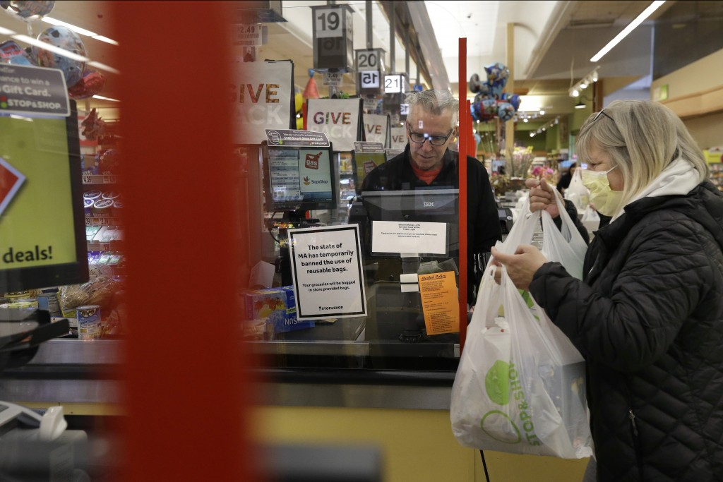 Cashier George Wallace, of Quincy, Mass., center, works behind a plastic shield as a shopper, right, places groceries in a cart, Thursday, March 26, 2...
