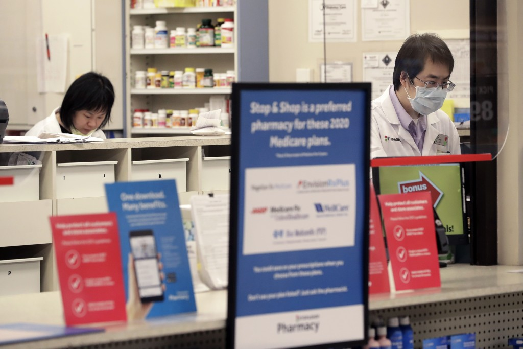 A pharmacist, right, stands behind a plastic shield at a grocery store, Thursday, March 26, 2020, in Quincy, Mass. Grocery stores across the U.S. are ...