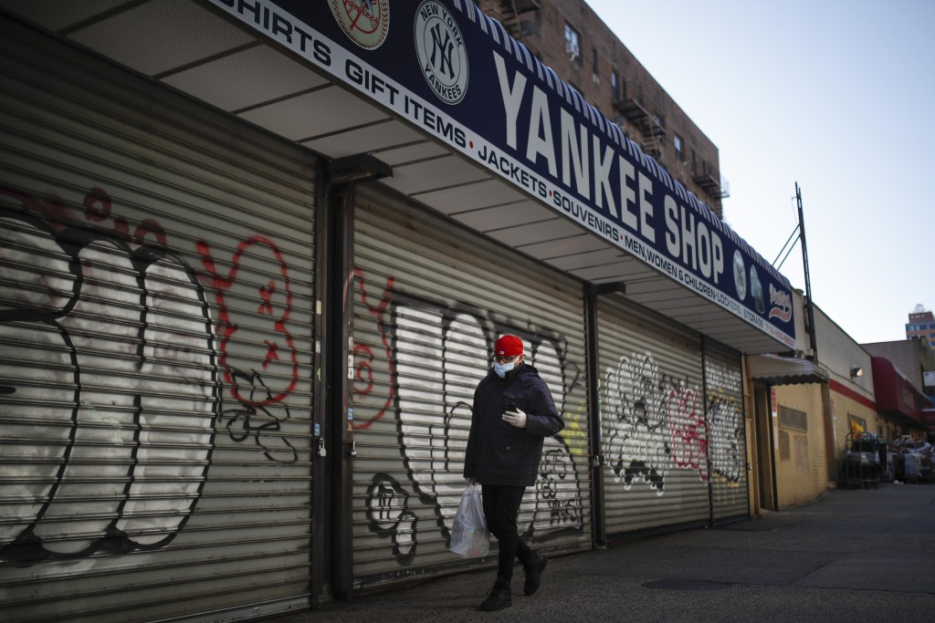 A pedestrian passes by a New York Yankees baseball souvenir shop, March 26, 2020, in the Bronx borough of New York. To baseball fans, opening day is a...