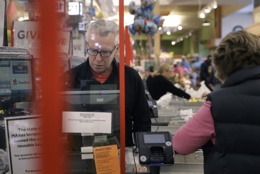Cashier George Wallace, of Quincy, Mass., center, works while standing behind a plastic shield Thursday, March 26, 2020, at the checkout in a grocery ...