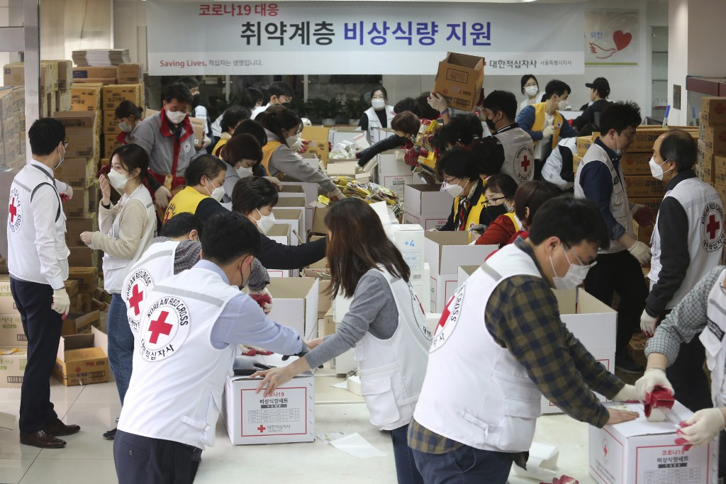 Red Cross workers prepare emergency relief kits packed with basic necessities for delivery to impoverished people experiencing difficulties amid the s...