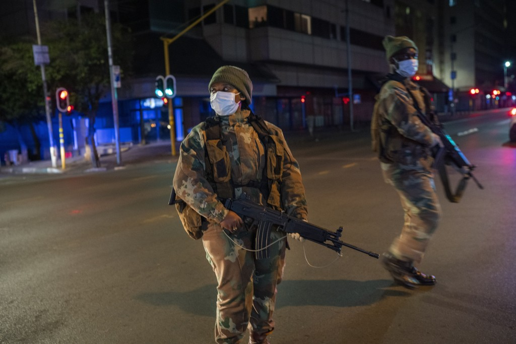 South African Defense Forces patrol downtown Johannesburg, South Africa, Friday, March 27, 2020. Police and army started patrolling moments after Sout...