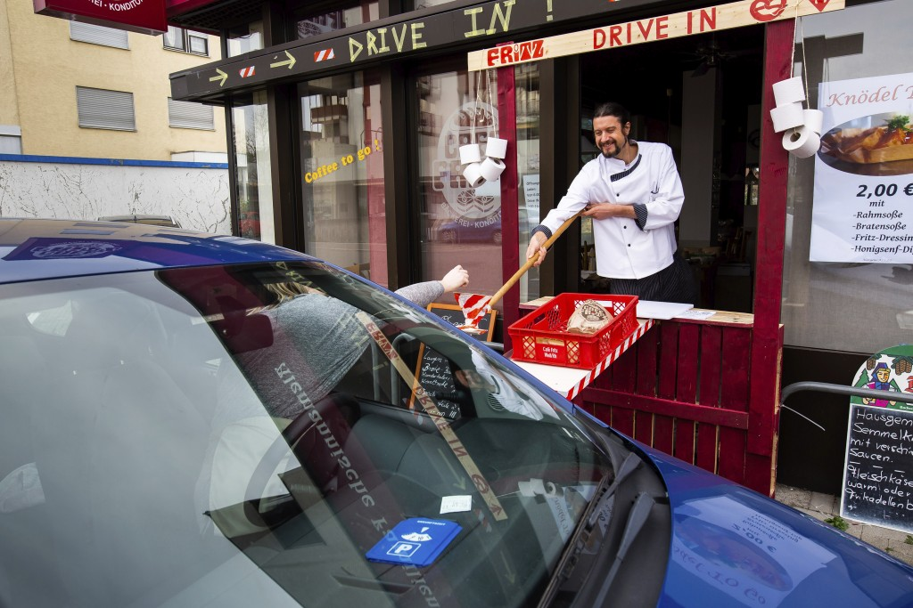 Master baker Simon Fritz accepts cash from a customer at the window of the improvised drive-in of his bakery with the help of a self-construction, in ...