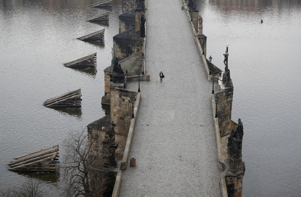 A woman walks across the nearly-empty Charles Bridge in Prague, Czech Republic, Friday, March 20, 2020. The government has approved further dramatic m...