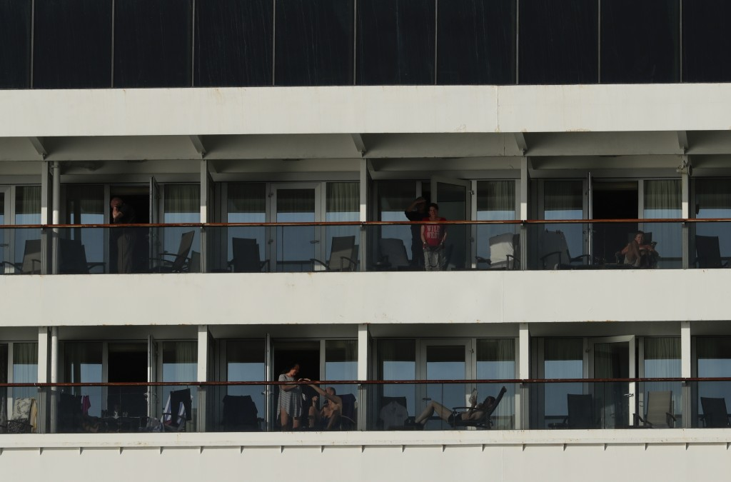Passengers stand on balconies of the Zaandam cruise ship, anchored in the bay of Panama City, Friday, March 27, 2020. Several passengers have died abo...