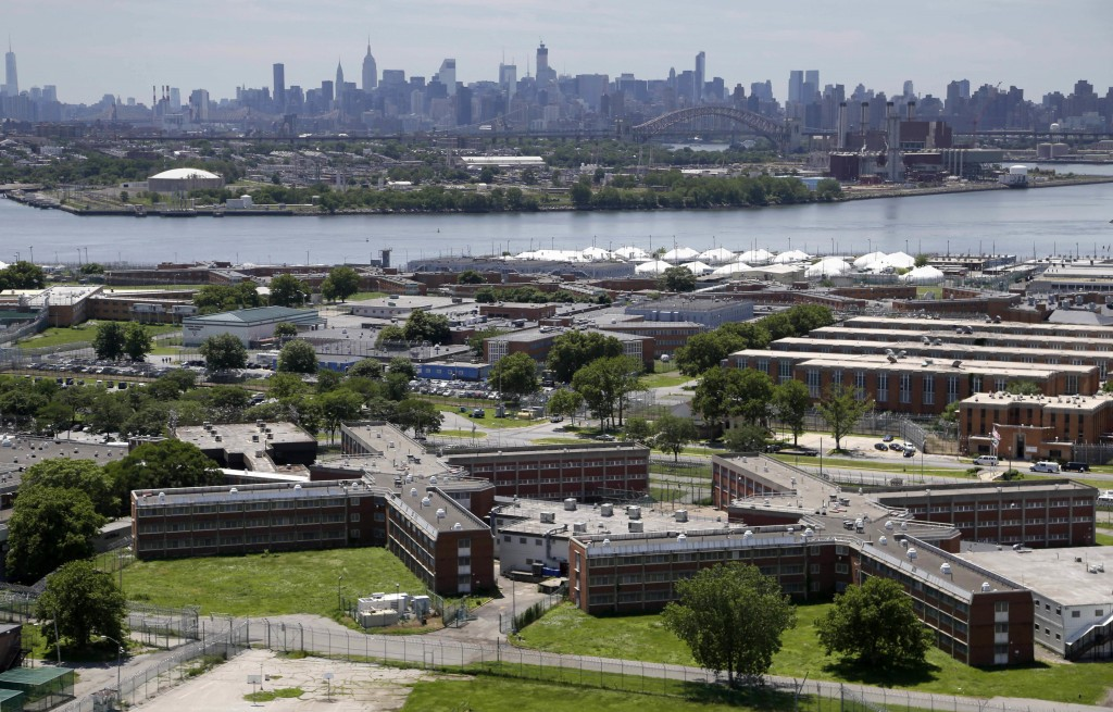 FILE - This June 20, 2014 file photo shows the Rikers Island jail complex in New York with the Manhattan skyline in the background. Health experts say...