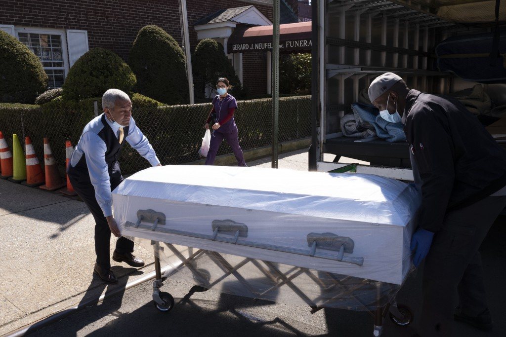 Omar Rodriguez, left, with the Gerard Neufeld Funeral Home, works with William Samuels who was delivering caskets to the Queens business, Friday, Marc...