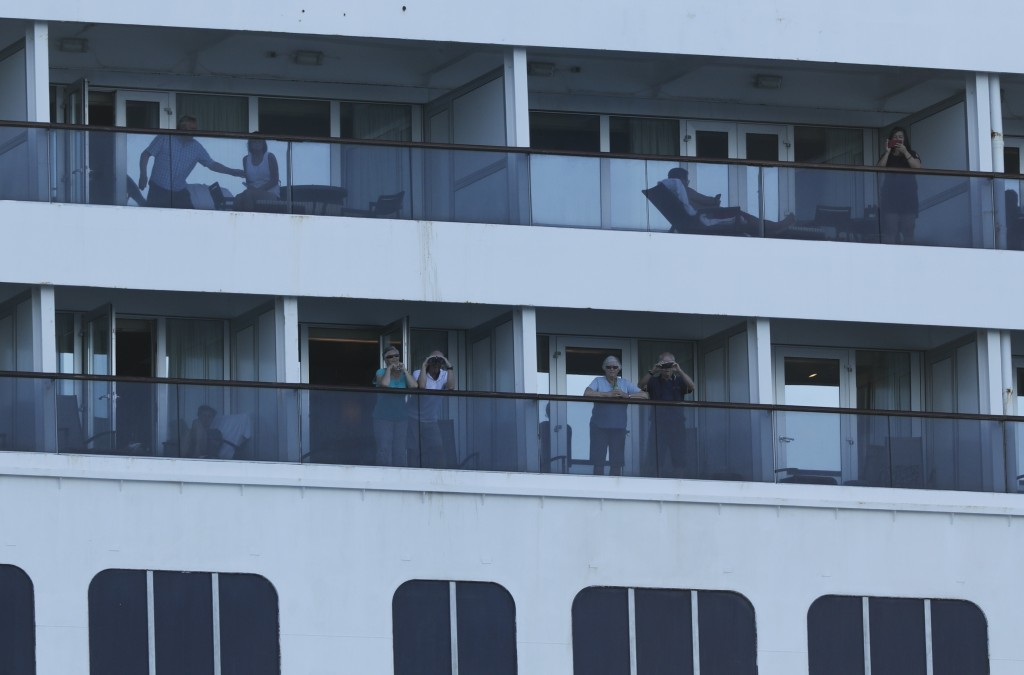 Passengers look out from the Zaandam cruise ship, anchored in the bay of Panama City, Friday, March 27, 2020. Several passengers have died aboard the ...